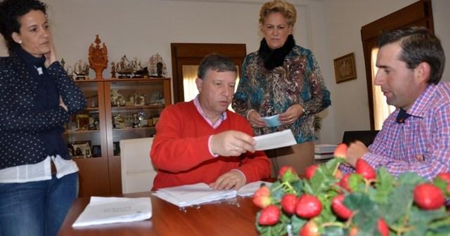 El alcalde de Palos entrega uno de los cheques de ayuda.
