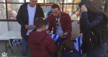 Futbolistas del Recreativo firmando autógrafos a los niños.