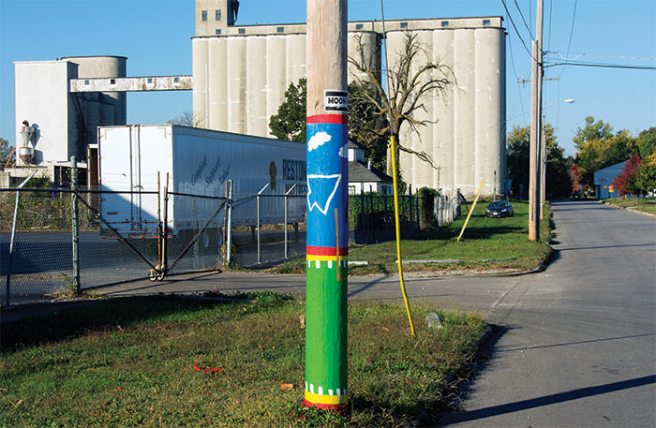 Had Edward Hopper happened upon this decorated pole in front of the majestic abandoned grain elevators he might have chosen another angle to paint.  Admittedly, the raw American commercial landscape may be an acquired taste, but adding silly doodles to power poles does not domesticate it.