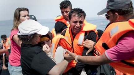 A volunteer helps a Syrian woman that collapsed while her husband cries as they arrive aboard a dinghy after crossing from Turkey, on the island of Lesbos, Greece, Monday, Sept. 7, 2015.