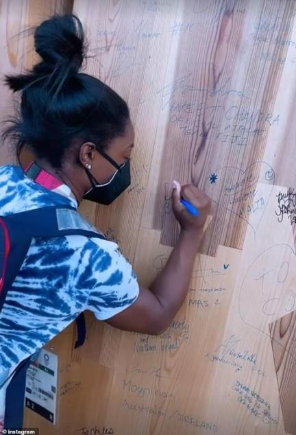 Defending champion Simone was seen scribbling her name on a wall of athletes' autographs