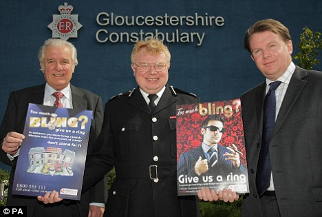 Gloucestershire's Chief Crown Prosecutor Adrian Foster, Chief Constable Timothy Brain and Crimestoppers Board Member John Cripps holding the new 'bling' posters