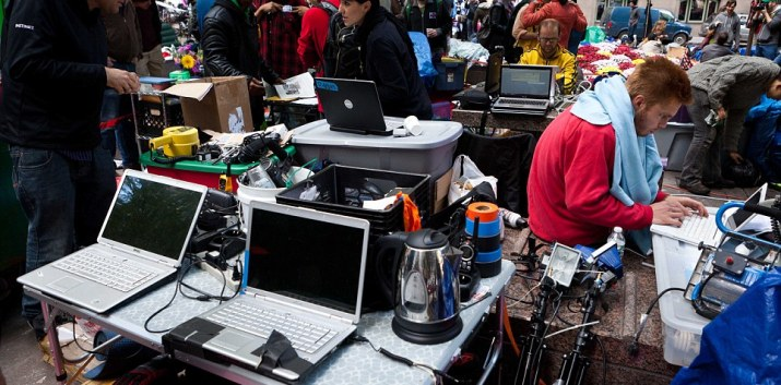 Protestors at Occupy Wall Street's media area coordinate news updates on laptop computers powered by a portable gas-powered generator in Manhattan's financial district's Zuccotti Park