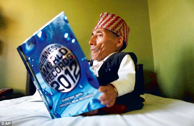 Nepal's Chandra Bahadur Dangi, 72, reads the Guinness World Records 2012 after officially becoming the world's shortest man