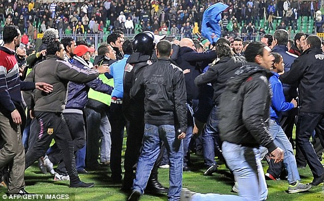 Chaos: Egyptian football fans rush to the pitch during the riots. Another 52 people are awaiting sentencing