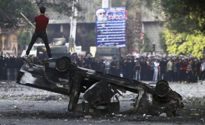 Fired up: In Cairo, a protester shouts slogans as he stands on a burnt car during clashes with riot police along a road leading to the U.S. embassy, near Tahrir Square in Cairo