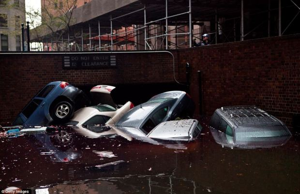 Destruction: Cars floating after being pushed out a flooded basement during last night's battering