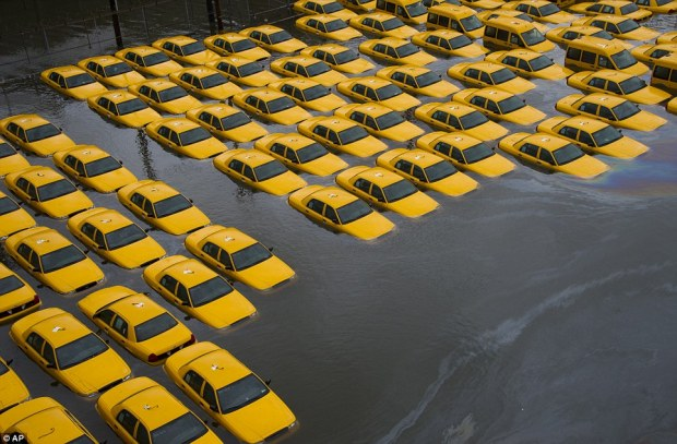 Fleet in the floods: Yellow cabs in a parking lot are surrounded by water after Superstorm Sandy struck Hoboken, New Jersey