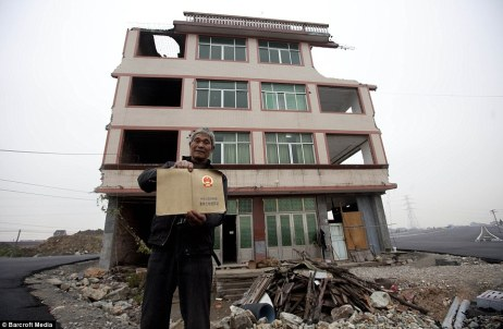 Proof: Mr Baogen stands in front of his home holding the certificate that states he owns the land beneath it, meaning that he and his wife can't be forced to move away