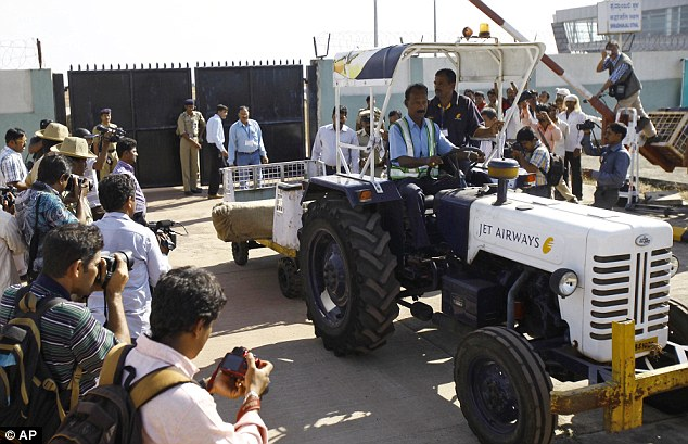 Moved: A casket containing the body of Ms Saldanha is shifted in a tractor trolley after it arrived at the airport