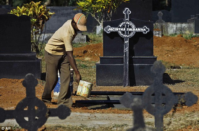 Before the ceremony: A worker prepares the grave of Ms Saldanha in Shriva north of Mangalore, India