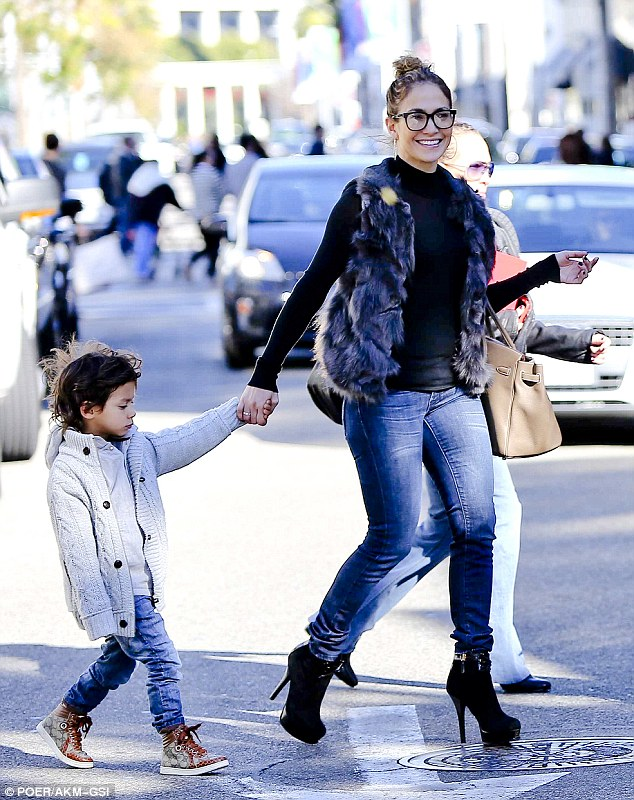 Stylish: Jennifer was fashionably outfitted in skinny jeans, stiletto boots and furry waistcoat, but obviously felt the need for more clothes