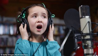 Singing her heart out: A little girl holds her headphones as she joins in the charity version of Over The Rainbow with other Sandy Hook children