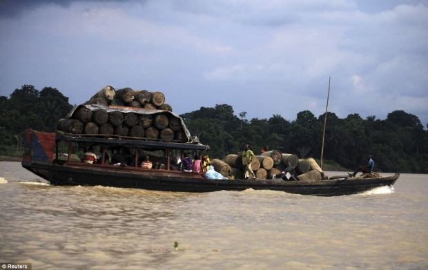 People travel on a locally built passenger boat loaded with oil containers through a creek on the River Nun
