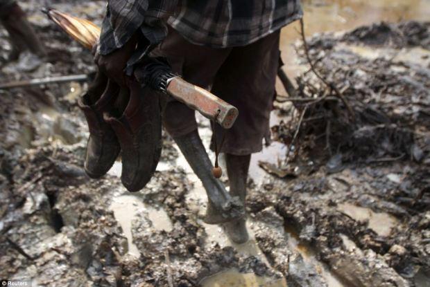 A man walks through farmland polluted with oil in the Kalaba community, near Yenagoa