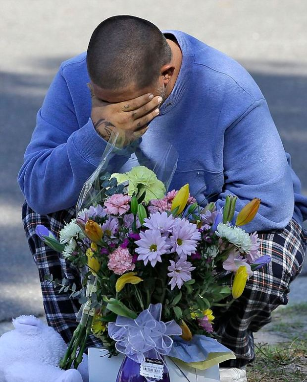 Gone: Brother Jeremy Bush reacts after placing flowers and a stuffed animal at a makeshift memorial in front of a home where a sinkhole opened up underneath a bedroom late Thursday evening and swallowed sibling Jeffrey in Seffner, Florida