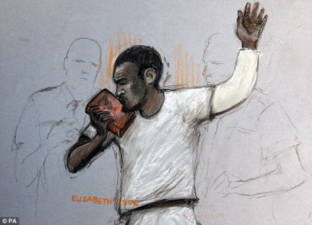 Unusual: Michael Adebolajo made a series of gestures in the dock at Westminster Magistrates' Court, including kissing the Koran while pointing the the sky