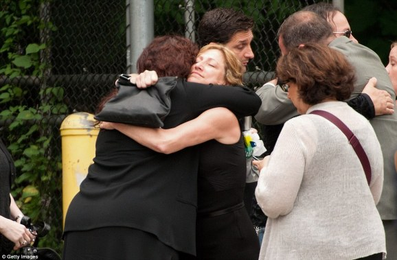 Embrace: Actress Edie Falco, who played James Gandolfini's on stage wife, Carmela, in The Sopranos hugs a fellow mourner after the funeral for the actor