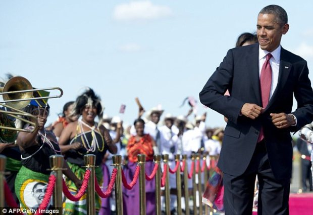 Festive: The President was seen dancing along to the music on the red carpet at the airport