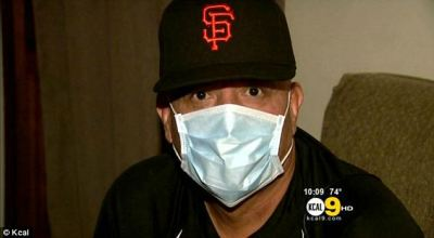 A masked cancer patient making a withdrawal at his bank was almost arrested after being mistaken ...