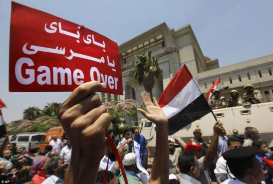 Game over: Egyptians celebrate in front of the constitutional court after Egypt's chief justice Adly Mansour was sworn in as the nation's interim president today