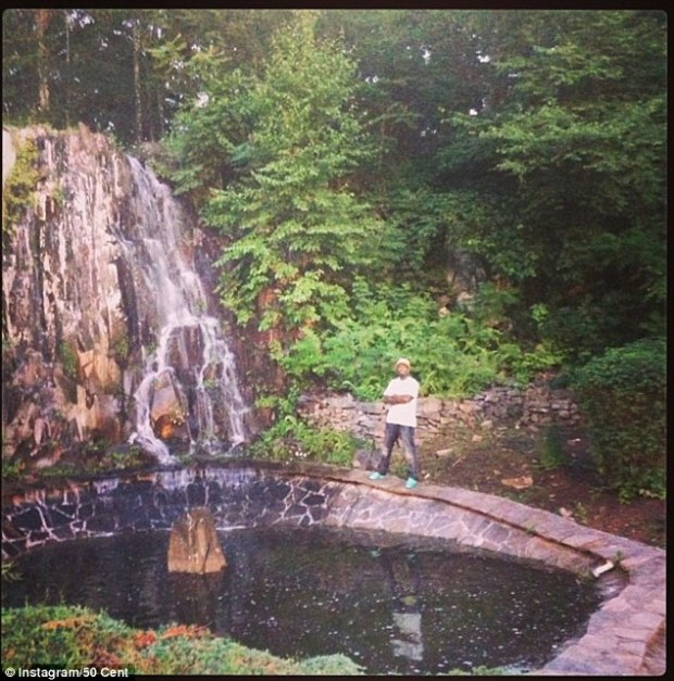 Grandiose: 50 is seen posing in front of his waterfall in his lavish back garden