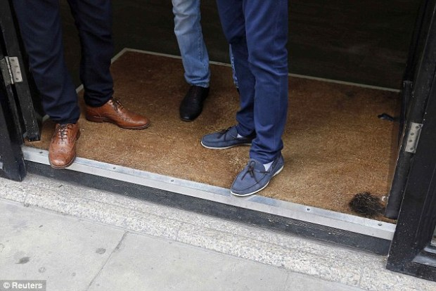 Scorched: Men stand in the doorway of a barbers shop, which has a burn mark on the carpet in London. It was reported that the carpet was set alight from sunlight reflected by the Walkie Talkie tower
