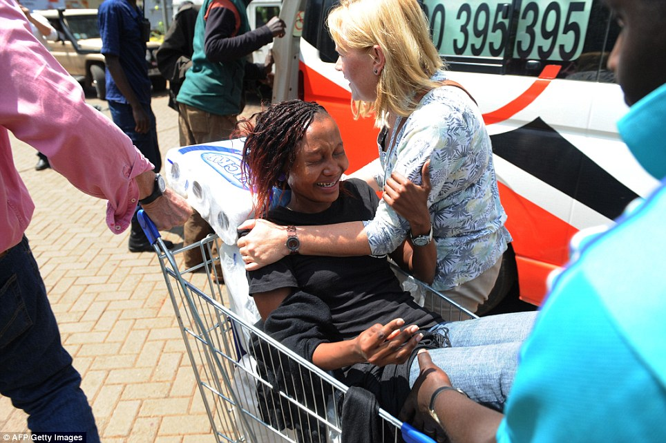 Rescue: A woman is shipped to an ambulance in a shopping trolley by centre staff