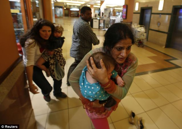 Escape: Women carrying children run for safety as armed police hunt gunmen who went on a shooting spree in Westgate shopping centre
