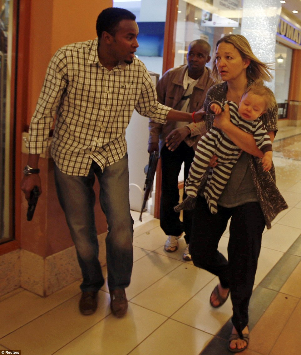 Rescue: Armed police guide a woman carrying a child to safety at Westgate Shopping Centre in Nairobi after terrorists stormed the building