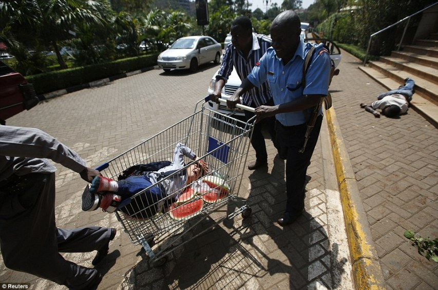 Make-shift: An injured woman is wheeled out of the shopping center in a shopping cart