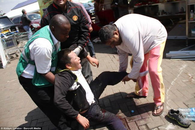 Helping hands: An injured man is carried out of the Westgate shopping center after Saturday's attack