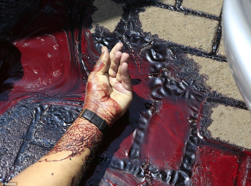 Pools of blood everywhere: This close up shows the hand of a man killed by the gunmen