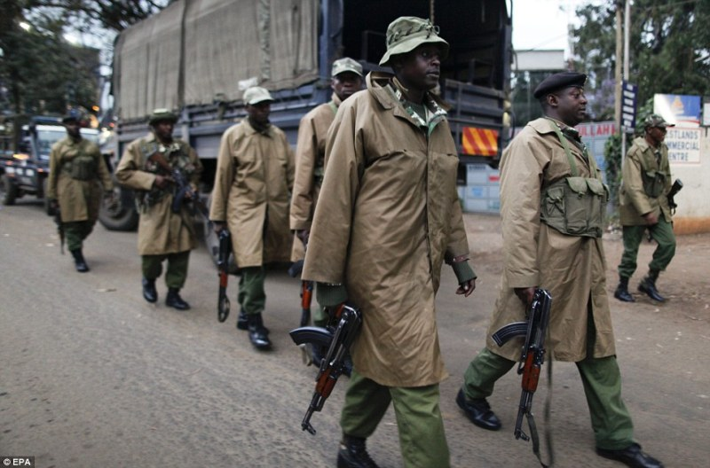 Kenyan paramilitary officers walk towards a small shopping arcade adjacent to the Westgate shopping mall where the hostage situation continues in Nairobi, Kenya on Sunday