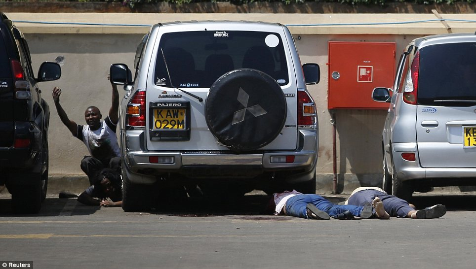 Ordeal: People come out from hiding under a car next to bodies in a car park as police search for the armed radicals