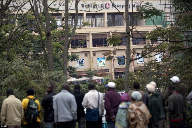 Waiting and Watching: Onlookers gather on a hill to observe the Westgate Mall after a bout of heavy gunfire just after dawn in Nairobi, Kenya Monday, Sept. 23, 2013