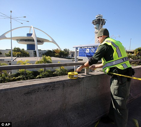 A police officer closes a road at the Los Angeles International Airport. Flights were suspended as the aiport was placed on lockdown