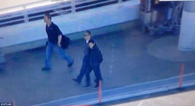 A man is led away by police in handcuffs from Los Angeles International on Friday following the shooting. It is unclear where this man is a suspect