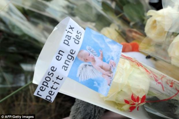 Tributes: A bouquet of white roses with a note reading 'rest in peace little angel' is left on the beach