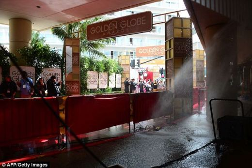 Black rain: The reportedly stinking black water poured onto press as they awaited Hollywood's greatest luminaries to parade down the Golden Globes red carpet--the sprinkler system had evidently been set off by an overheated lighting rig