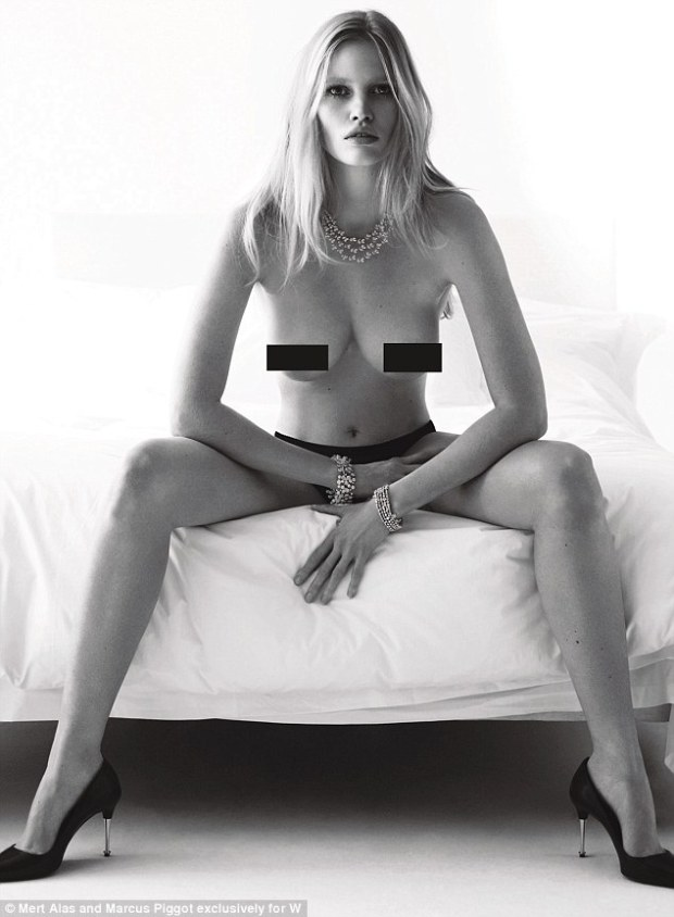 Blonde beauty: Lara Stone was pictured sitting on the edge of the bed with her bare breasts exposed, wearing just a pair of knickers and killer heels