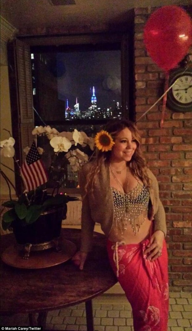 Exotic: Mariah Carey showed off her ample cleavage and washboard abs in a beaded crop top and pink sarong in an image she tweeted at 2am from New York on Saturday