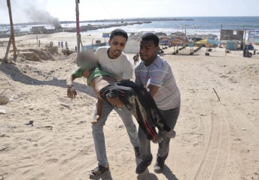 Tragic: Palestinian men carry the body of a young boy, who medics said was killed by a shell fired from an Israeli naval gunboat, on a beach in Gaza City this morning