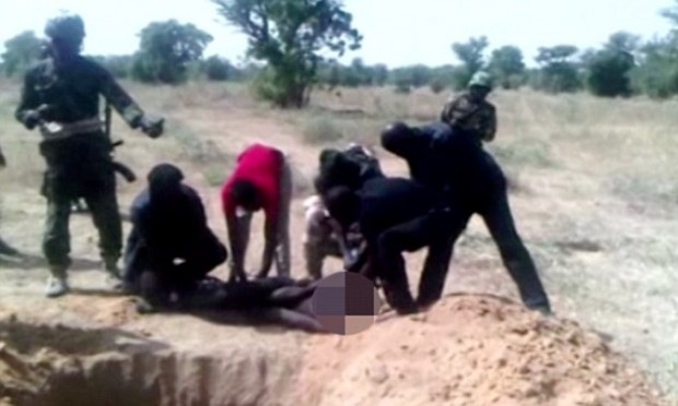 In another horrific scene, a man is held down by the feet and shoulders next to the grave before he is brutally executed with a combat knife. Amnesty International says the video shows 'graphic evidence of multiple war crimes' being carried out in Nigeria