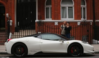 Impressed by-passers stop to take photos of a Ferrari parked in Knightbridge. The cars have been spotted just one day after a series of luxury vehicles were spotted on the streets of Cannes, southern France