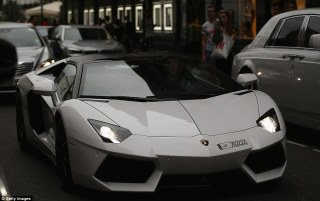 Shoppers stop to take photos of a Lamborghini Aventador which was driving through west London. The vehicles are tailor-made versions of famous models from luxury-brand car manufacturers