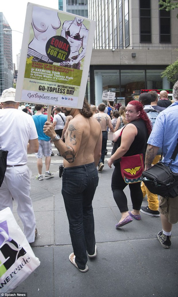Supportive: Men got in on the act in New York, marching for women's rights to bare their chests