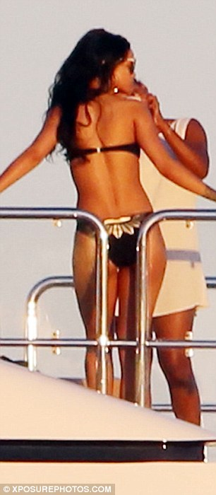 Say cheese: Stripping down to a simple but sexy black and grey bikini with gold accents, the hitmaker had her friend play photographer as she posed in an impromptu photo shoot