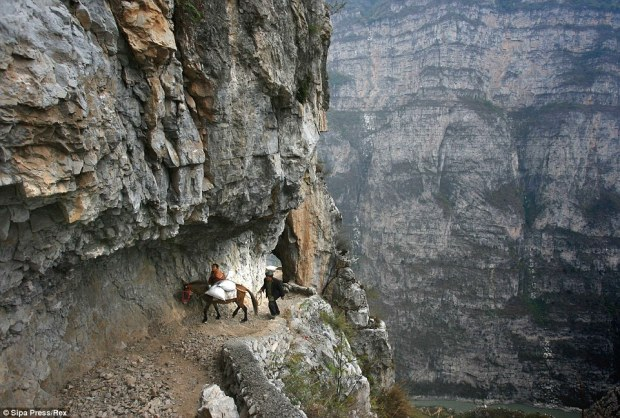 On the edge: This young child and his grandfather have to negotiate a narrow, rocky mountain pass on the way to a primary school in Sichuan province, China. The Gulu village's school is located halfway up the mountain and is the most remote in the world