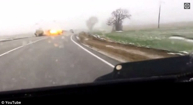 Gone in a flash: The dash cam footage  shows the vehicle speeding along with a police siren sounding in the background - All of a sudden the car bursts into flames and explodes sending debris all over the road